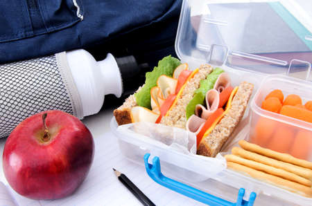brown box: School bag, healthy lunch box and apple with books and pencil