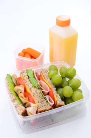 Healthy lunch box with turkey and ham sandwich with grapes, carrots and orange juice photo