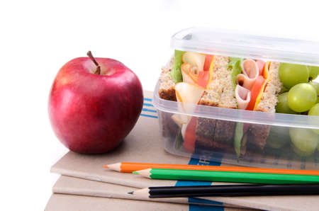 Healthy lunch box with sandwich and apple on books and pencils  photo