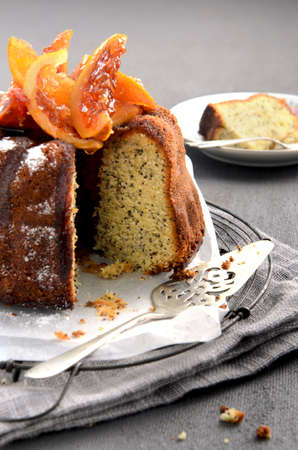 Poppyseed bundt cake with a slice removed, topped with sweetened grapefruit and orange sements, styled by professional food stylist  Stock Photo - 15555580