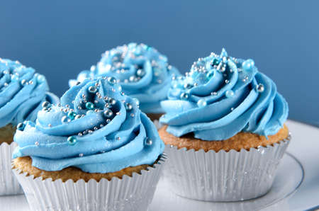 Cupcake dessert with blue icing frosting and silver ball decorations