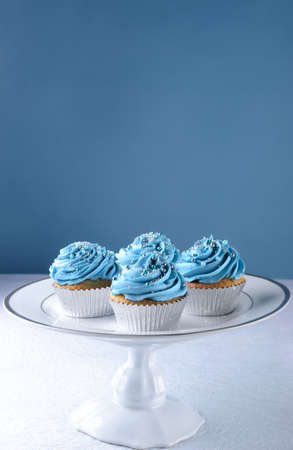 Cupcake dessert with blue icing frosting and silver ball decorations on a cake stand  photo
