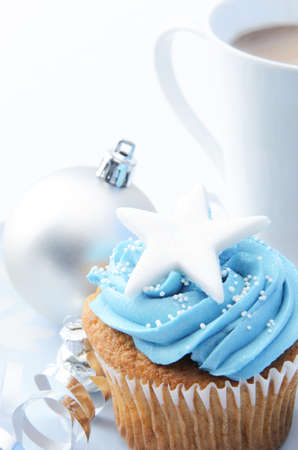 Christmas treat mug of hot chocolate, frosty icy blue theme cupcake with silver xmas bauble decorations  photo