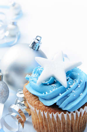 Blue icing frosted cup cake with silver christmas ornaments and decorations, plenty of copyspace Stock Photo - 15540968