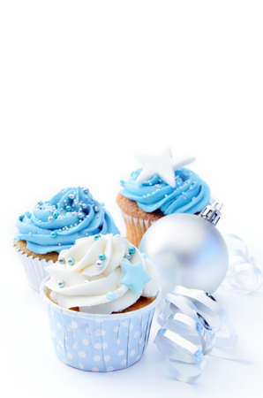 Christmas cakes with blue and white frosting and silver bauble decorations  photo