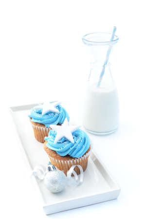 Festive holiday cool tone blue winter cupcakes with large star, christmas decorations and milk bottle  photo