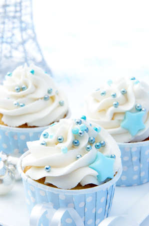 Christmas party cupcakes with white frosting and baby blue decorations  photo