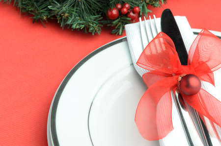 Christmas place setting with red ribbon and bauble  photo