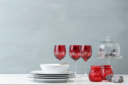 Modern christmas decoration table display with crockery and festive holiday red wine glasses photo
