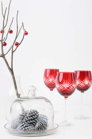Christmas interior decorating minimalist elegant style, silver white pine cones in glass dome with festive red wine glasses Stock Photo - 15549877
