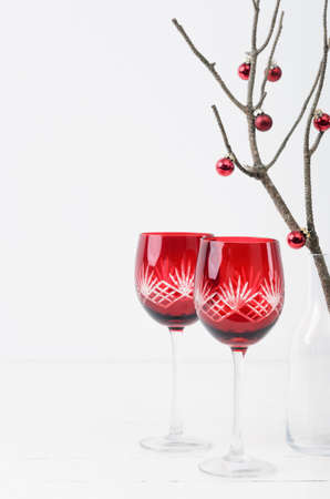 Red festive christmas wine glasses on table with minimalist christmas tree Stock Photo - 15549769