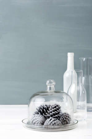 Minimalist christmas interior decoration with clear glass bottles, white pine cones and grey background, plenty of copy space photo
