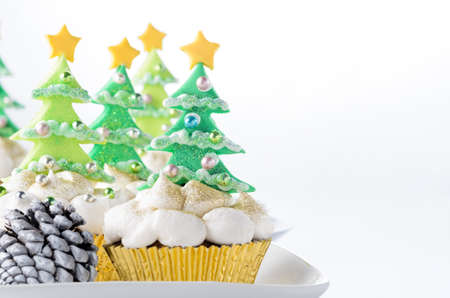 Christmas tree cupcakes with buttercream icing as snow on white background  photo