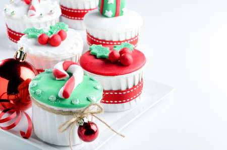 Seasonal festive christmas mini dessert cupcakes in traditional red green decorative symbols elements  photo