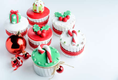 sweet treat: Seasonal festive christmas mini dessert cupcakes in traditional red green decorative symbols elements  Stock Photo