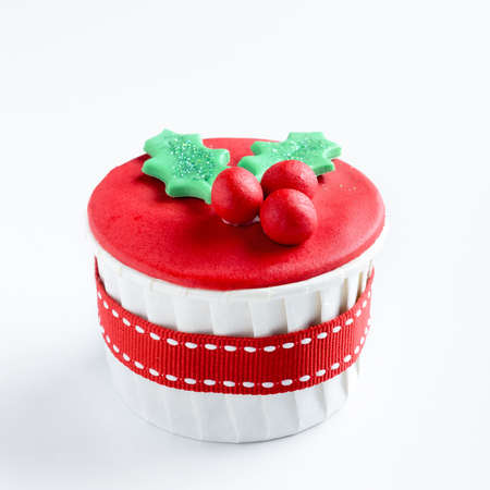 Christmas cupcake in traditional red green colours with mistletoe, decorative element  photo