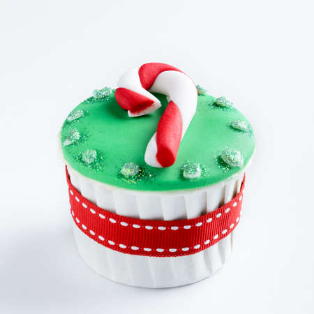 Christmas cupcake in traditional red green colours with candy cane decorative element  photo