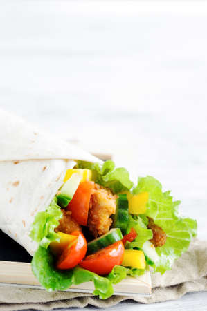 Crumbed chicken tortilla wrap with fresh healthy green salad, tomatoes, cucumber and bell peppers Stock Photo - 15549731