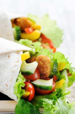 Crumbed chicken tortilla wrap with fresh healthy green salad, tomatoes, cucumber and bell peppers Stock Photo - 15549849