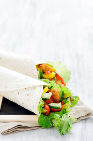 Crumbed chicken burrito lunch wrap with fresh healthy green salad, tomatoes, cucumber and bell peppers Stock Photo - 15540948