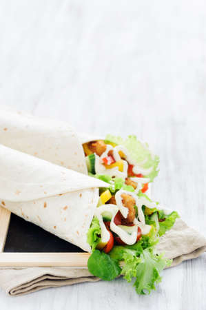 Crumbed chicken tortilla wrap with fresh healthy green salad, tomatoes, cucumber and bell peppers photo