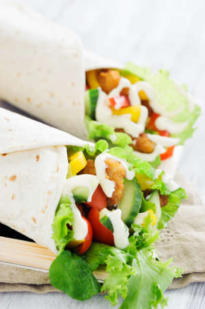 Light lunch chicken burrito wrap with fresh healthy green salad, tomatoes, cucumber, bell peppers and mayonaise Stock Photo - 15549843