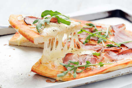 Slice of pizza lifted up with melted mozzarella, parma ham, rocket photo