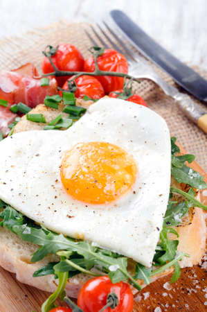 Big breakfast with egg, tomato, bacon and rocket on toast served on rustic wooden board  heart conscious photo
