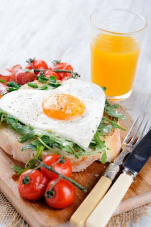 Big breakfast with egg, tomato, bacon and rocket on toast served on rustic wooden board with oj orange juice   heart conscious Stock Photo