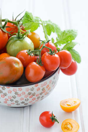 Close up tomatos in a bowl, cherry, roma, green, yellow, vine ripened with fresh green leaves  Stock Photo - 15541220