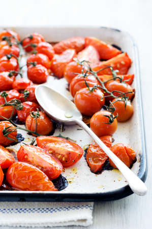 Baking tray filled with delicious juicy oven roasted tomatoes with large serving spoon, focus on front wedges of tomato Stock Photo - 15555908