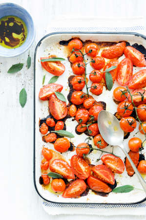 Baking tray filled with delicious juicy oven roasted tomatoes with fresh sage leaf herb and olive oil  photo