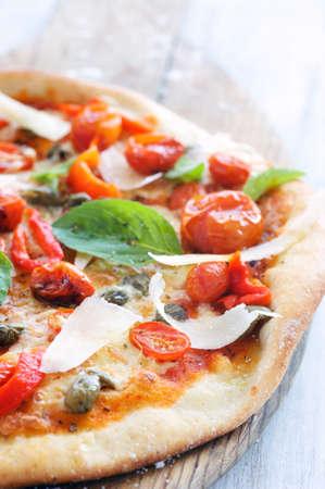 italienisches essen: Macro close up auf rustikale Pizza mit Ofen ger�steten Tomaten, Paprika, Kapern, Basilikum und rasierte K�se