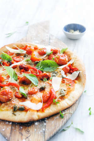 Fresh, handmade pizza with oven roasted tomatoes, peppers, capers, basil and shaved cheese  photo