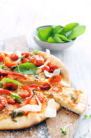Fresh, handmade pizza with oven roasted tomatoes, peppers, capers, basil and shaved cheese on rustic wooden board  photo