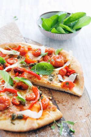 c�pres: Frais, pizza � la main avec des tomates r�ties au four, poivrons, c�pres, basilic et fromage ras� Banque d'images