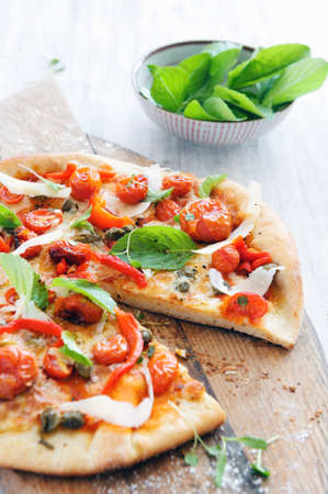 Fresh, handmade pizza with oven roasted tomatoes, peppers, capers, basil and shaved cheese  Stock Photo
