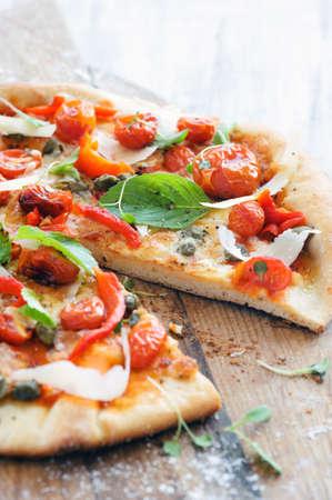 신선한 허브, 구운 토마토, 고추, 케이 퍼, 면도 치즈와 함께 이탈리아 피자 스톡 사진