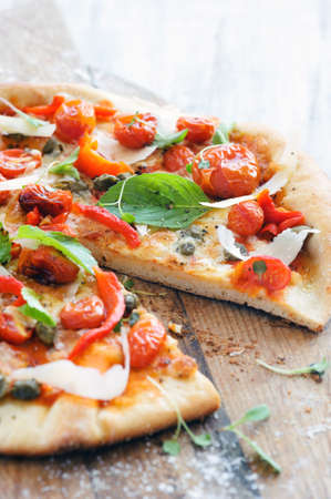 Italian pizza with fresh herbs, roasted tomatoes, peppers, capers and shaved cheese Stock Photo