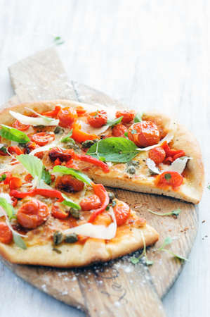 Fresh, handmade pizza with oven roasted tomatoes, peppers, capers, basil and shaved cheese on rustic wooden board  Stock Photo - 15555948