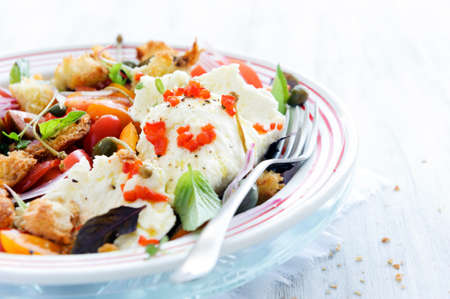 Fresh mozzarella cheese with mix salad, cherry tomatoes, peppers, basil and croutons  photo