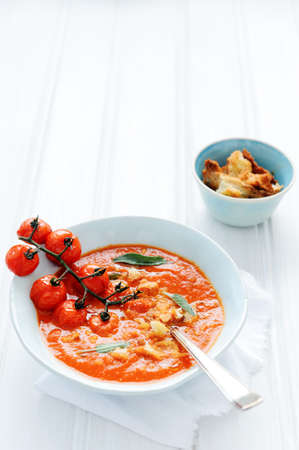 Bowl of fresh delicious tomato soup with croutons and sage garnish on white rustic surface; healthy eating  Stock Photo - 15549781