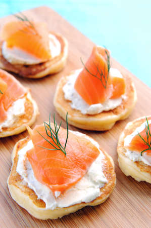 Appetising smoked salmon and cream cheese blinis on a wooden platter  photo