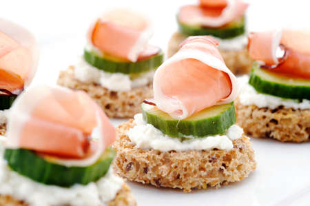 Mini toasts topped with cottage cheese, cucumber and ham  photo