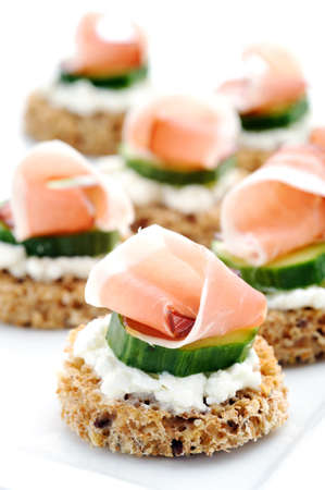 Mini toasts topped with cottage cheese, cucumber and ham