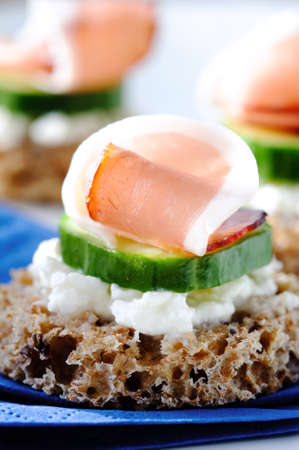Close up on a smoked meat canape with cucumber and cottage cheese photo