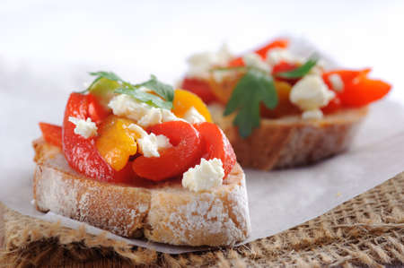 rustic food: Macro shot of slices of bagutte topped with roasted red and yellow peppers with feta cheese  Stock Photo