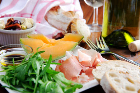 Gourmet platter of prosciutto, rocket and cantaloupe with bread and wine  photo