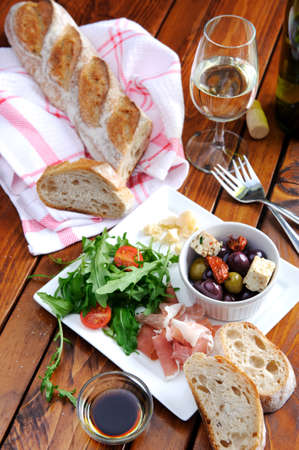 Romantic dinner for two; italian antipasto platter with parma ham, rocket, olives, baguette and wine  photo