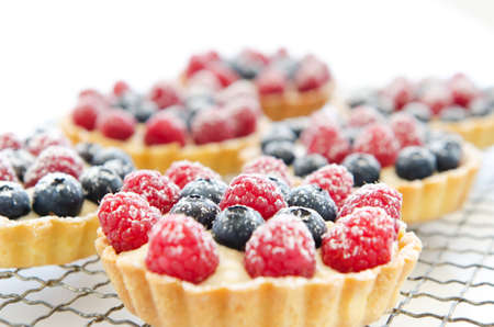 Horizontal orientation of a cooling tray of tarts topped with raspberries and blueberries, sprinkled with icing sugar photo